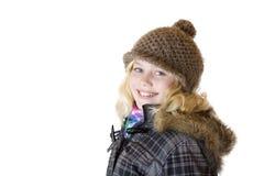 La chica joven con el casquillo, la bufanda y la chaqueta sonríe feliz Imagenes de archivo