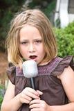 La chica joven con el micrófono/canta Fotografía de archivo libre de regalías
