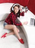 La chica joven con el ordenador portátil escucha la música Foto de archivo