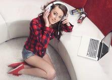 La chica joven con el ordenador portátil escucha la música Fotografía de archivo libre de regalías