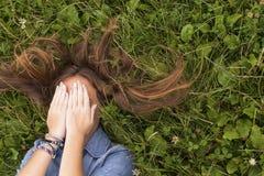 La chica joven con el pelo largo, cerrándose observa mientras que miente en la hierba verde Relájese Imagen de archivo