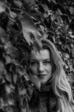 La chica joven con el pelo largo que se coloca cerca de la pared con las uvas salvajes deja día soleado del otoño Imagen de archivo libre de regalías