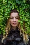 La chica joven con el pelo largo que se coloca cerca de la pared con las uvas salvajes deja día soleado del otoño Fotografía de archivo