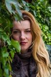 La chica joven con el pelo largo que se coloca cerca de la pared con las uvas salvajes deja día soleado del otoño Imagen de archivo