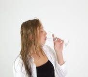 La chica joven con el pelo marrón bebe el agua Imágenes de archivo libres de regalías