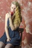 La chica joven con el pelo rizado rubio en un vestido largo con los lunares con el oso de peluche come la manzana Fotos de archivo