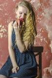 La chica joven con el pelo rizado rubio en un vestido largo con los lunares con el oso de peluche come la manzana Imágenes de archivo libres de regalías