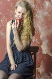 La chica joven con el pelo rizado rubio en un vestido largo con los lunares con el oso de peluche come la manzana Fotografía de archivo libre de regalías