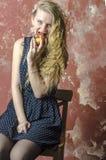 La chica joven con el pelo rizado rubio en un vestido largo con los lunares con el oso de peluche come la manzana Foto de archivo libre de regalías