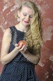La chica joven con el pelo rizado rubio en un vestido largo con los lunares con el oso de peluche come la manzana Imagen de archivo