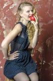 La chica joven con el pelo rizado rubio en un vestido largo con los lunares con el oso de peluche come la manzana Imagenes de archivo