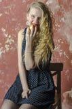 La chica joven con el pelo rizado rubio en un vestido largo con los lunares con el oso de peluche come la manzana Imagen de archivo libre de regalías