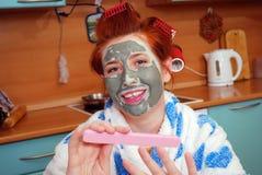 La chica joven con el pelo rojo en bigudíes de pelo con un paquete de cara de la arcilla en cocina manicure foto de archivo libre de regalías