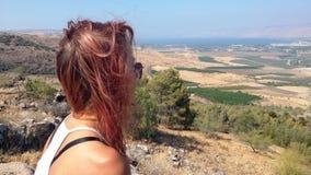 La chica joven con el pelo rojo mira el valle Imagenes de archivo
