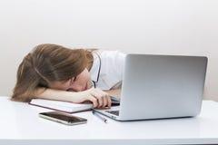 La chica joven con el pelo rubio en una blusa blanca puso su cabeza en la tabla delante de un ordenador portátil imagen de archivo