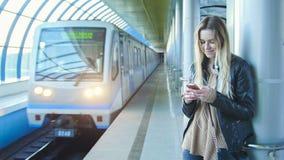 La chica joven con el pelo rubio largo del artilugio en la chaqueta de cuero endereza la situación en metro contra la perspectiva Fotos de archivo