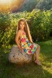 La chica joven con el pelo rubio largo se sienta en una piedra en los rayos de un sol brillante Imágenes de archivo libres de regalías