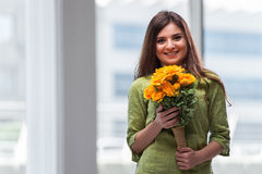 La chica joven con el presente de flores Fotos de archivo libres de regalías
