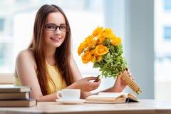 La chica joven con el presente de flores Foto de archivo libre de regalías