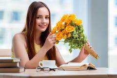 La chica joven con el presente de flores Imagen de archivo libre de regalías