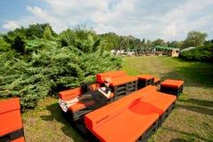 La chica joven con el teléfono móvil tiene resto en el sofá en partido al aire libre en la zona verde de la ciudad Fotos de archivo libres de regalías