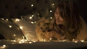 La chica joven con el terrier de Yorkshire del perro rodeó la luz de la Navidad almacen de video