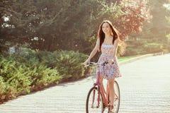 La chica joven con la bicicleta en parque Foto de archivo