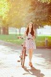 La chica joven con la bicicleta en parque Foto de archivo libre de regalías