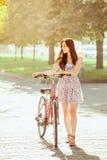 La chica joven con la bicicleta en parque Fotos de archivo