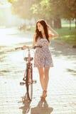 La chica joven con la bicicleta en parque Imagenes de archivo