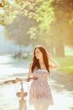 La chica joven con la bicicleta en parque Imagen de archivo libre de regalías