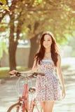 La chica joven con la bicicleta en parque Fotos de archivo libres de regalías