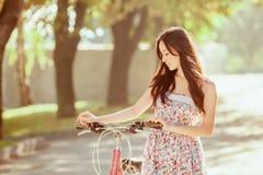 La chica joven con la bicicleta en parque Fotografía de archivo libre de regalías