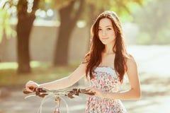 La chica joven con la bicicleta en parque Imágenes de archivo libres de regalías