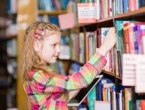 La chica joven con la tableta elige un libro en la biblioteca Imágenes de archivo libres de regalías