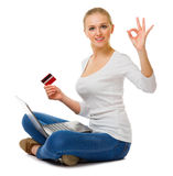 La chica joven con la tarjeta del ordenador portátil y del plástico muestra gesto aceptable Fotografía de archivo