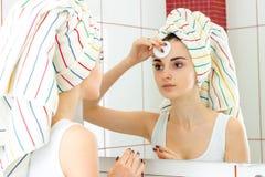 La chica joven con la toalla en el pelo mira en el espejo y el maquillaje que frota de la cara Foto de archivo