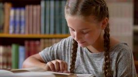 La chica joven con las coletas está leyendo en la biblioteca almacen de metraje de vídeo