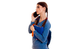 La chica joven con las coletas vale el dar vuelta de lado en una chaqueta azul y dice por el teléfono Imagenes de archivo