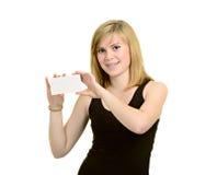 La chica joven con los corchetes sostiene el papel en blanco aislado en blanco detrás Foto de archivo