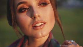 La chica joven con los ligones fáciles del humor del otoño en la cámara en parque almacen de metraje de vídeo