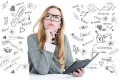 La chica joven con los vidrios lee un eBook en fondo a mano Fotografía de archivo libre de regalías