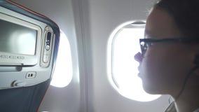 La chica joven con los vidrios y los auriculares mira el vídeo en el monitor incorporado a la butaca en la cabina del aeroplano
