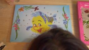 La chica joven con la mamá hace el mosaico diy en la tabla manía Visión superior almacen de video