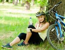 La chica joven con un agua de botella en su mano está descansando después de biking Fotos de archivo libres de regalías