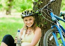 La chica joven con un agua de botella en su mano está descansando después de ciclo Fotografía de archivo libre de regalías