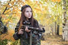 La chica joven con un arma está en el bosque del otoño Fotos de archivo libres de regalías