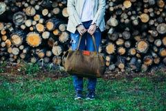 La chica joven con un bolso de cuero en una pared de registros Foto de archivo