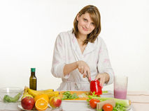 La chica joven con un placer vegetariano corta la pimienta Imagen de archivo libre de regalías
