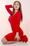 La chica joven con una figura hermosa en un vestido rojo de moda en miniskirt ceñido y los tacones altos y plataforma rojos se vi Imágenes de archivo libres de regalías